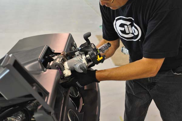 "An Elio Motors' technician installs a steering column assembly into the instrument panel of the first Elio E-Series vehicle, which will be used for testing and validation. Safety is a ""must-have"" for the Elio design, which calls for three airbags (one steering-wheel mounted), a reinforced roll-cage frame, and crush zones 50 percent larger than those on similar vehicles. Image courtesy of Elio Motors."