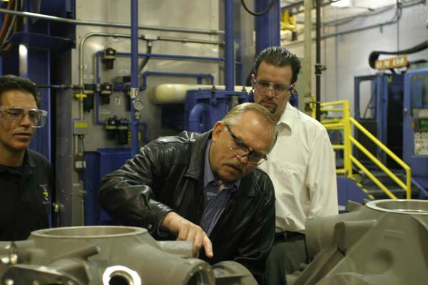 John Ratzenberger examines a part with employees at a Sikorsky factory. Image courtesy of John Ratzenberger.