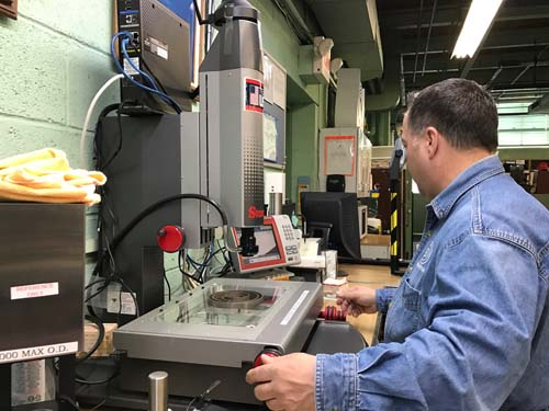 Brewster Washers President Sal Freda, Jr. demonstrates a measuring device used in the plant to measure the precision of a company's part. The metrology department appears to have six measuring devices ready for use, as well as historic hand-held micrometers