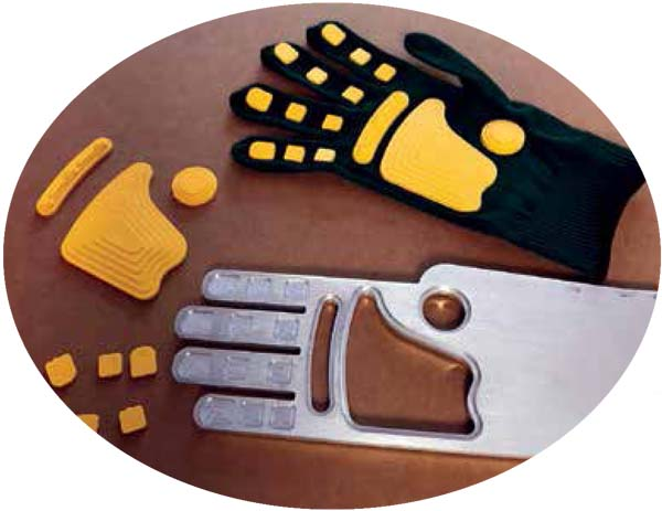 The yellow injection molded parts (left) are glued to the glove (at top) to create a Fan Hand. The metal piece (bottom right) is a jig used by a worker at Coarc to properly locate each position for the plastic parts to be glued to the glove. Photo by Mark Langlois.