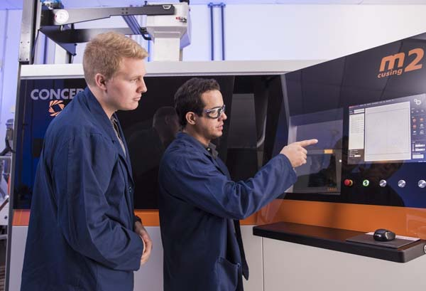 Sintavia Applications Engineer Shawn Morgan and Additive Technician Juan Manjarres work with one of the metal additive manufacturing company's newest machines an M2 cusing from Concept Laser